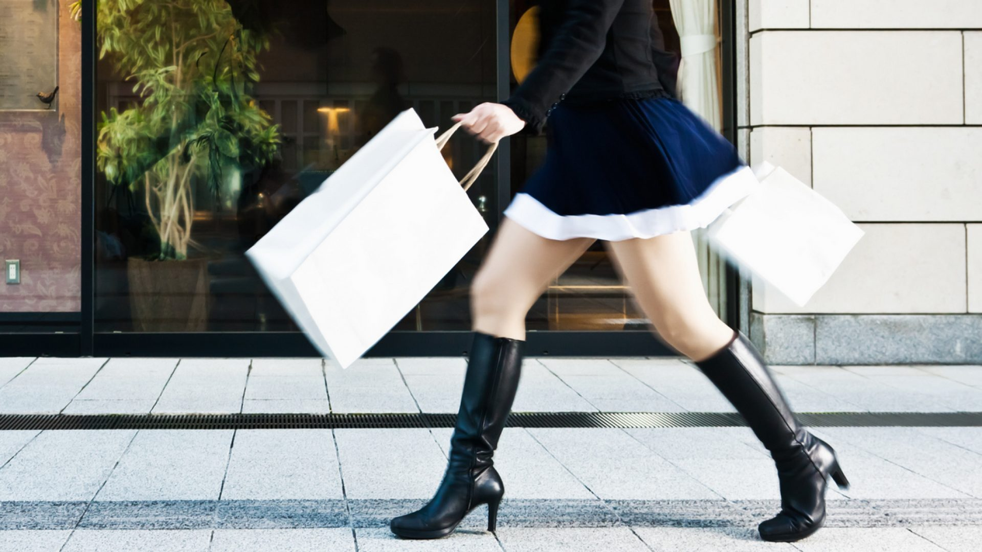 Woman strolling down the street wearing boots and swinging shopping bags.