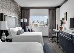 Una habitación de hotel con una cama y un televisor con pantalla plana
