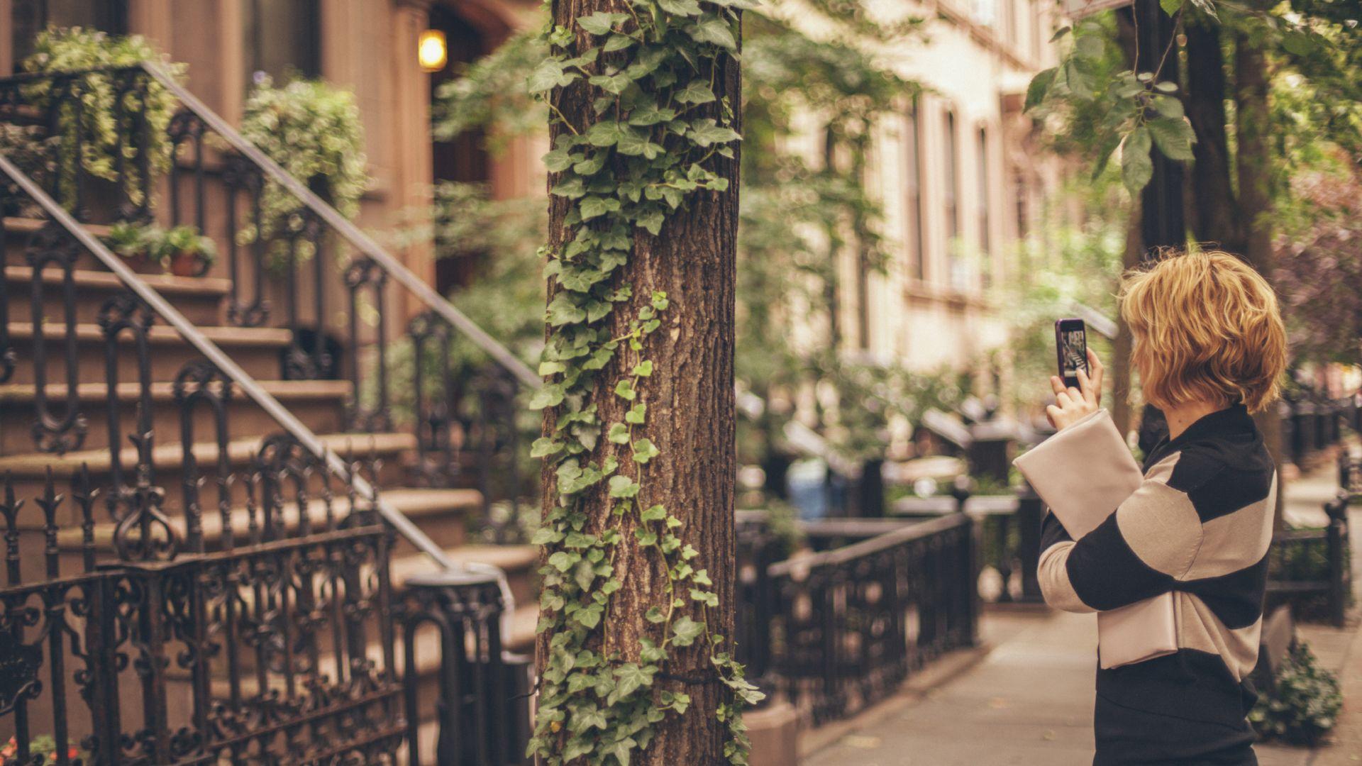 Une femme prend des photos des maisons Brownstones de New York avec son téléphone