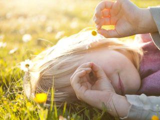 Una niñarecostada en un campo de margaritas
