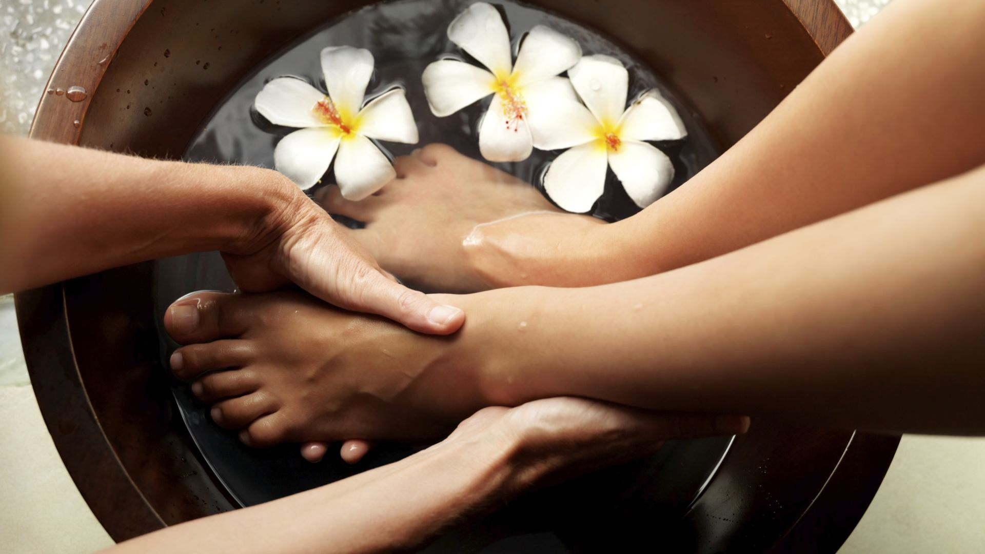 Foot treatment at spa - with flowers and feet immersed in bowl of water.