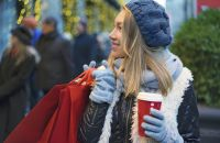 Una mujer con guantes de invierno, sombrero y bufanda sosteniendo una taza roja de café y bolsas de compras rojas.