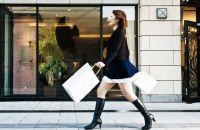 Mujer caminando por la calle con botas y llevando bolsas de compras.