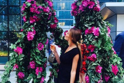 Una persona parada frente a una flor
