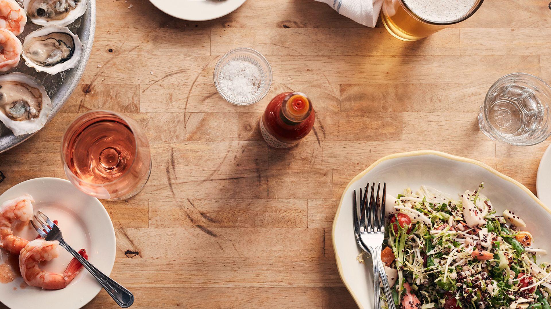 Loews Hotels - Un plato con mariscos y una cerveza sobre una mesa de madera