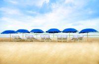 Una sombrilla azul en una playa con arena