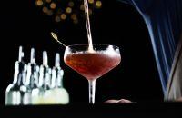 Un barman sirviendo Boulevardier en un vaso