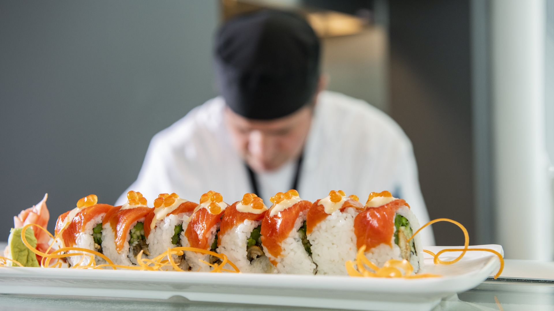 A Person Sitting At A Table With A Plate Of Sushi