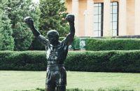 Estatua de un hombre parado delante de un edificio