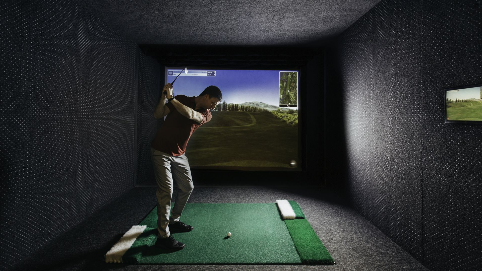 Man golfing in virtual golf simulator