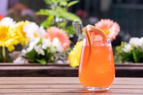 Un vaso de jugo de naranja junto a un jarrón con flores, sobre una mesa