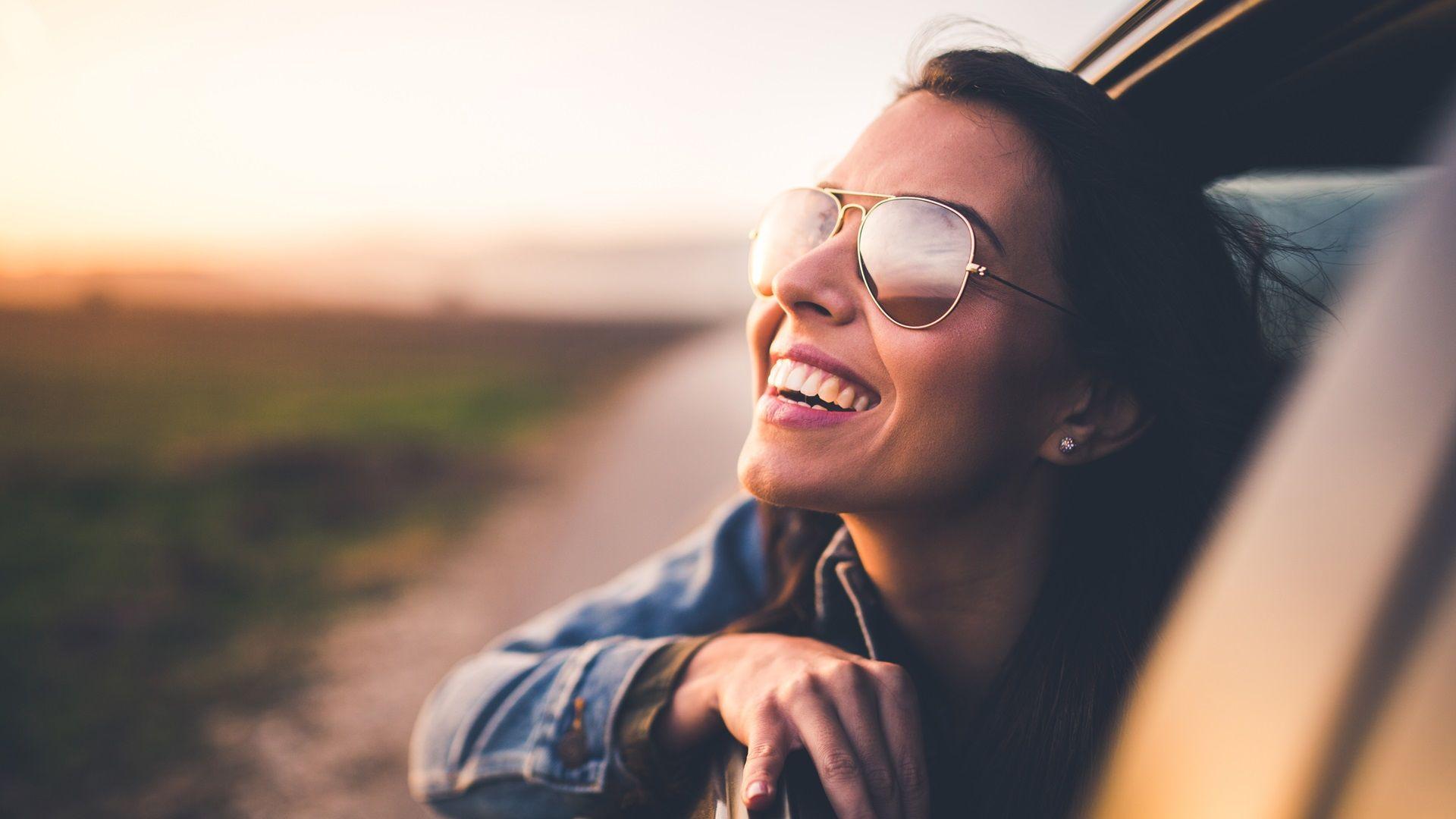 Frau mit Sonnenbrille lächelt in die Kamera