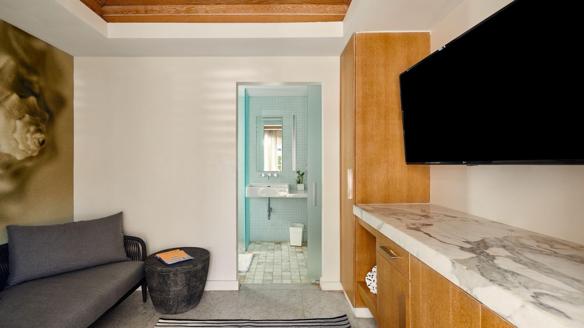 Una habitación con un sofá y una mesa delante de un espejo