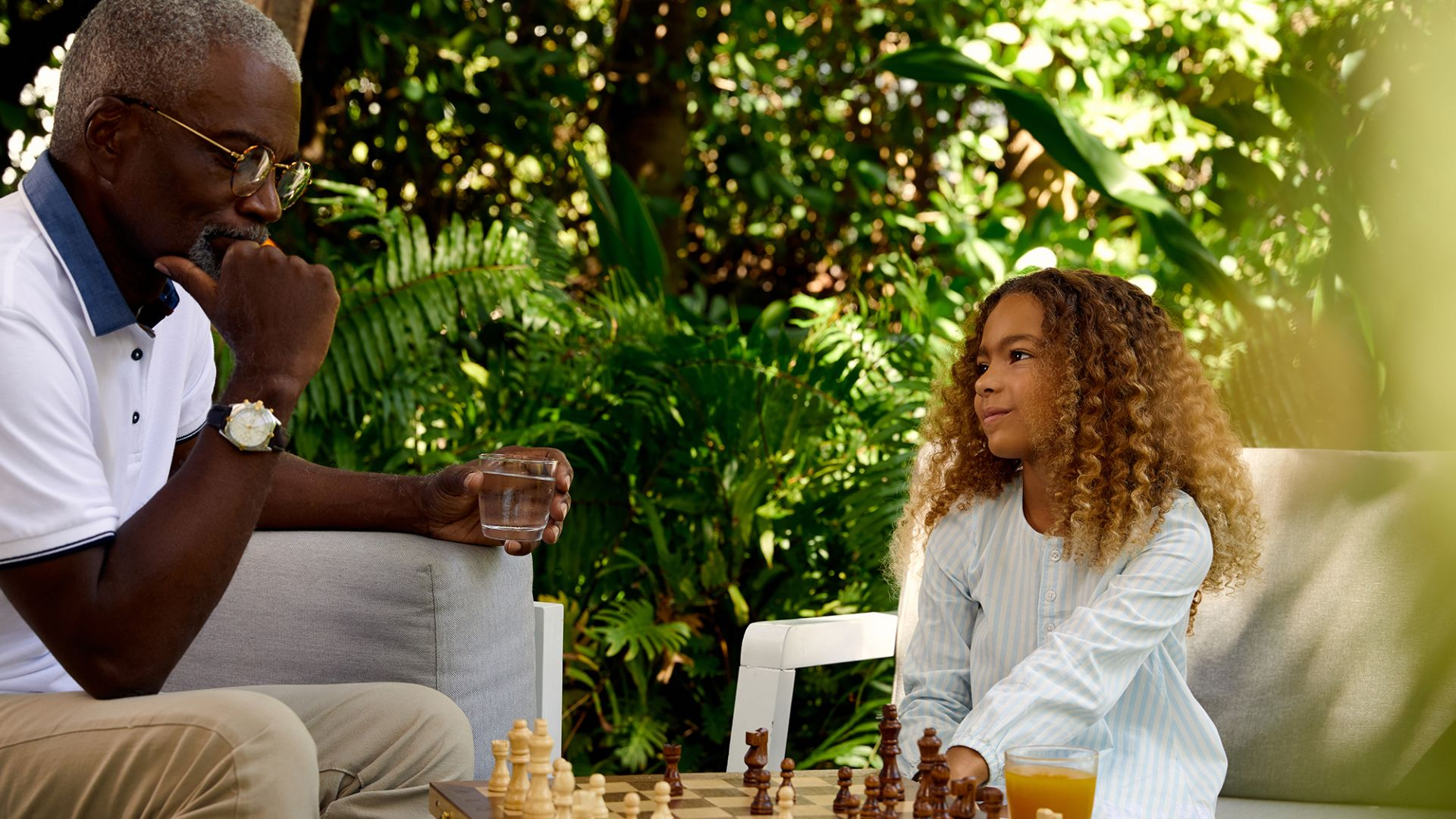 Una niña y su abuelo jugando al ajedrez al aire libre