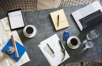 Escritorio con laptop, tablet, cuaderno, papeles, reloj, cafés y agua