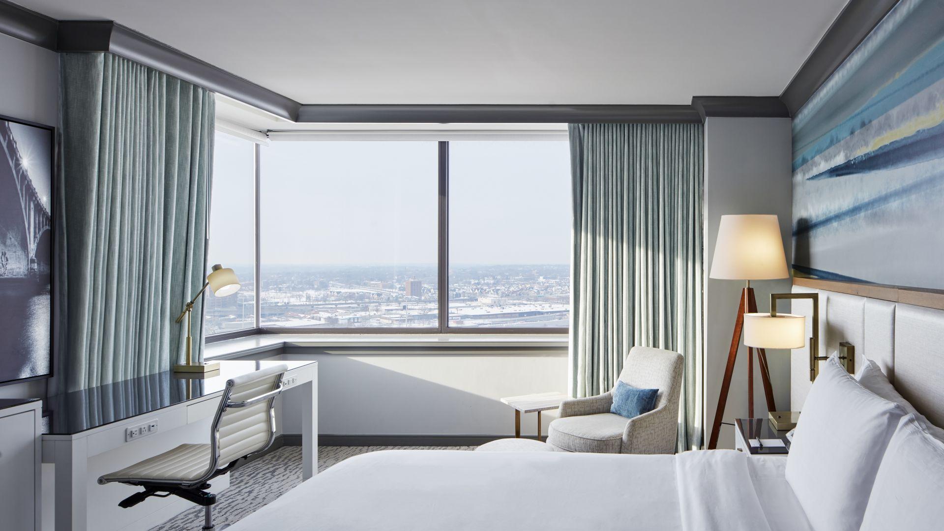 Una habitación con una cama y un ventanal