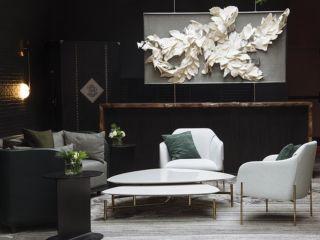 Una sala de estar con muchos muebles y un jarrón sobre la mesa