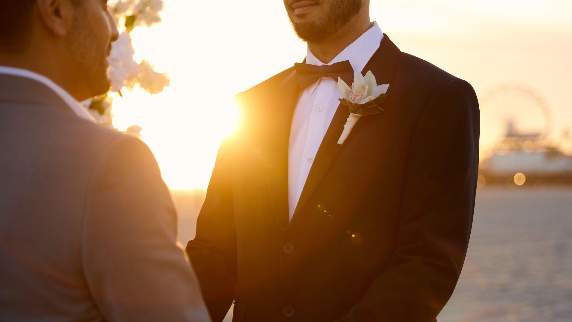 Una persona con traje y corbata sosteniendo la mano en alto