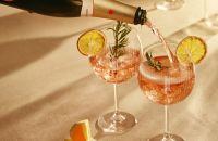 Un plato de comida y copas de vino sobre una mesa